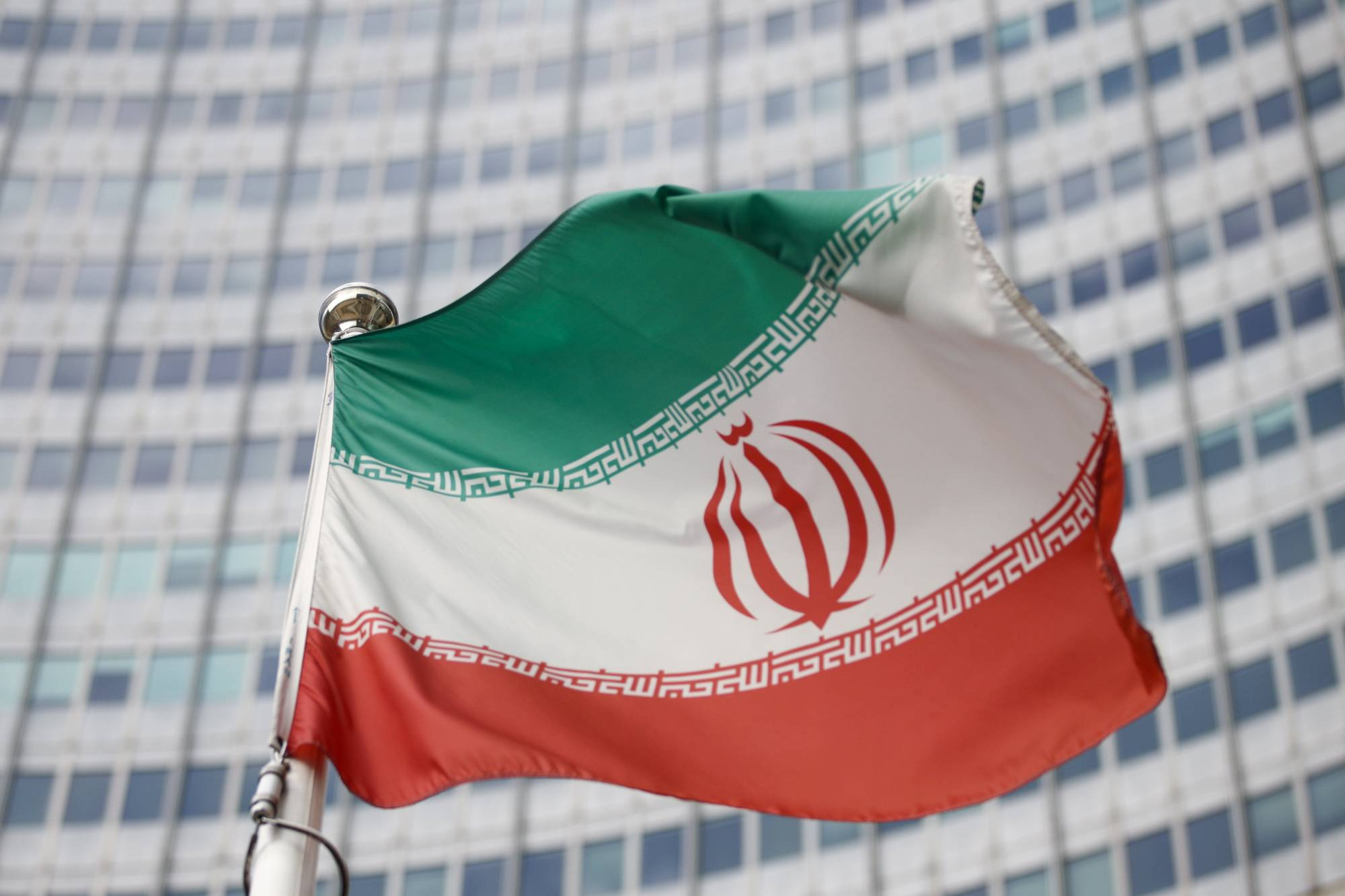 The Iranian flag waves in front of the International Atomic Energy Agency's headquarters in Vienna on March 1. The United States said Friday it offered 'very serious' ideas on reviving the Iran nuclear accord but was waiting for Tehran to reciprocate as partner nations voiced optimism following talks in Vienna. | REUTERS