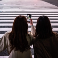 A woman films with her mobile phone on a street in Tokyo's Shibuya Ward on Friday. | AFP-JIJI