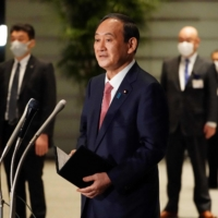 Prime Minister Yoshihide Suga speaks to reporters after announcing that Tokyo, Kyoto and Okinawa will be put under coronavirus pre-emergency measures, during a government task force meeting at the Prime Minister's Office in Tokyo on Friday.  | POOL / VIA AFP-JIJI