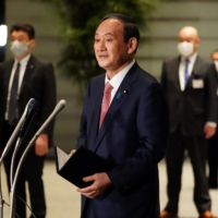 Prime Minister Yoshihide Suga speaks to reporters after announcing that Tokyo, Kyoto and Okinawa will have pre-emergency status under a new anti-virus law during a government task force meeting at the Prime Minister's Office in Tokyo on Friday. | POOL / REUTERS