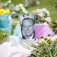 A picture of the late Prince Philip is placed among flowers outside Windsor Castle after his death at the age of 99, in Windsor, England, on Saturday.  | REUTERS