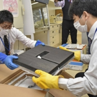 Officials check a box of the COVID-19 vaccine at a vaccination venue in Nagoya on Thursday. | KYODO