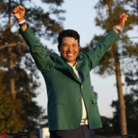 Hideki Matsuyama celebrates in the green jacket presented to the champion after winning the Masters in Augusta, Georgia, on Sunday.