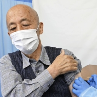 COVID-19 vaccinations for people age 65 and over started Monday at the Hachioji Municipal Government building in Tokyo. | POOL / VIA KYODO