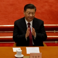 Chinese leader Xi Jinping applauds at the closing session of the Chinese People's Political Consultative Conference at Beijing's Great Hall of the People on March 10. Tensions between Beijing's approach and the democratic values underpinning the G7 are becoming increasingly hard to gloss over. | REUTERS