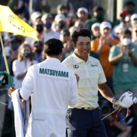 Hideki Matsuyama celebrates with his caddie after winning the Masters in Augusta, Georgia, on Sunday.