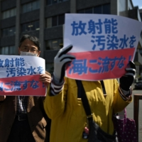 Activists take part in a protest against the government's plan to release treated water from the stricken Fukushima No. 1 nuclear plant into the sea, outside the Prime Minister's Office in Tokyo on Monday. | AFP-JIJI