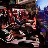 How Hong (left) of Canada tries out a driving simulator in the Formula One Esports League booth during the Consumer Electronics Show in Las Vegas on Jan. 7, 2020. | REUTERS