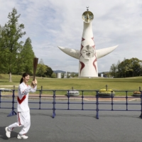 Olympic torch carried through empty Osaka park as COVID-19 cases rise