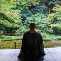 A Buddhist monk practices Zen meditation amid a natural setting. Don't expect the same amount of inner peace from most Japanese companies, however.