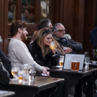 Customers dine at an outdoor seating area of a restaurant in Soho, London, on Monday, as nonessential retailers reopened after almost 100 days of lockdown, along with pubs and restaurants with outdoor space. | BLOOMBERG
