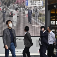 A large screen in Osaka shows news about the Olympic torch relay, which was held in an empty park in the prefecture amid a surge in coronavirus infections. | KYODO