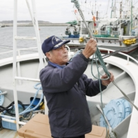 A fisherman takes care of his boat at a port in Namie, Fukushima Prefecture, near the crippled Fukushima No. 1 nuclear power plant. | KYODO