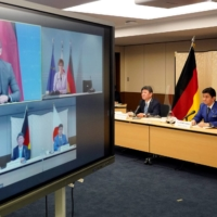 Japanese Foreign Minister Toshimitsu Motegi (center) and Defense Minister Nobuo Kishi attend a video conference with German Foreign Minister Heiko Maas (top left) and Defense Minister Annegret Kramp-Karrenbauer (top right) on Tuesday. | POOL VIA REUTERS