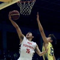 Alvark guard Taiki Osakabe (left) goes for a layup while dodging a block by Shibuya's You Nishino during a game in March. | KAZ NAGATSUKA