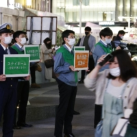 Officials from the Tokyo Metropolitan Government and local ward office stand near Shinjuku Station on Monday holding signs asking people to stay at home.