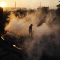 A Chinese laborer walks through steam next to a furnace and cooling pit at an unauthorized steel factory in 2016 in Inner Mongolia, China. | GETTY IMAGES / VIA BLOOMBERG