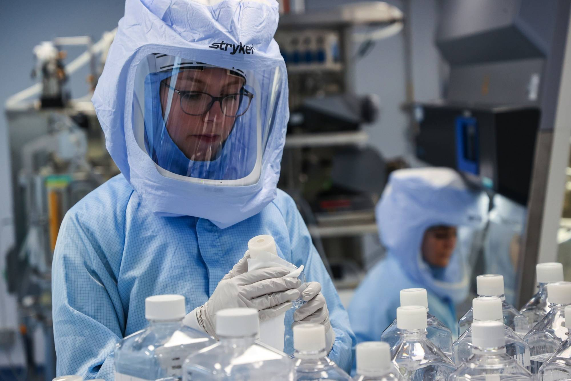 Employees prepare raw materials for messenger RNA, the first step in COVID-19 vaccine production, at the BioNTech SE laboratory in Marburg, Germany, in March.  | BLOOMBERG