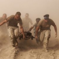 Members of the U.S. Navy carry a comrade wounded by an explosion to a helicopter in southern Afghanistan's Kandahar province in 2010. | REUTERS