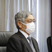 Bank of Japan Gov. Haruhiko Kuroda (left) attends a virtual meeting of the BOJ's regional branch managers on Thursday. | KYODO