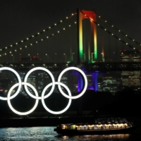 The Rainbow Bridge is illuminated with Olympic colors on Wednesday to mark 100 days until the Olympics. | REUTERS