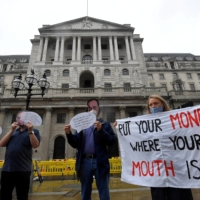 Environmental activists wear masks depicting Bank of England Gov. Andrew Bailey during a protest to encourage a green economy, outside of the Bank of England in the City of London in 2020. | REUTERS