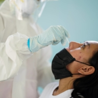 A health care worker takes a nasal swab sample from a person for a coronavirus test in Bangkok on Friday.  | REUTERS