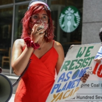 Mitzi Jonelle Tan, international spokesperson of Youth Advocates for Climate Action Philippines, speaks during a protest in front of a Standard Chartered Bank office in the financial district of Makati, near Manila, in March.   AFP-JIJI