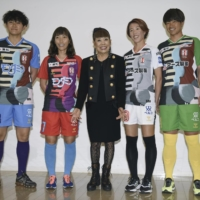 Designer Hiroko Koshino (center) poses with INAC Kobe players during a news conference in Kobe on Thursday. The players are wearing new uniforms that Koshino designed.  | KYODO