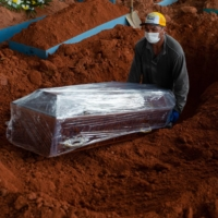 A cemetery worker lowers the coffin of a COVID-19 victim at the Nossa Senhora Aparecida cemetery in the city of Manaus, in Brazil's Amazon state, on Thursday. | AFP-JIJI