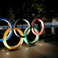 The Olympic rings are illuminated in front of National Stadium in Tokyo on Jan. 22. | REUTERS
