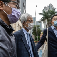 Martin Lee (center), founder of the Hong Kong Democratic Party, leaves the West Kowloon Magistrates Courts during a break in a mitigation and sentencing hearing in Hong Kong on Friday.  | BLOOMBERG