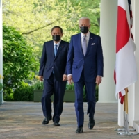 U.S. President Joe Biden and Prime Minister Yoshihide Suga walk to take part in a joint news conference in the Rose Garden of the White House in Washington on Friday.