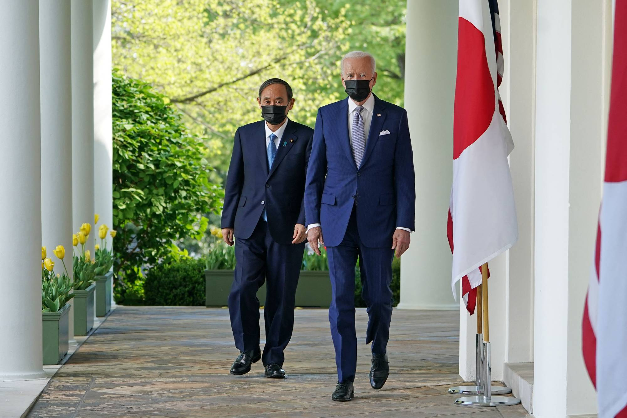 U.S. President Joe Biden and Prime Minister Yoshihide Suga walk to take part in a joint news conference in the Rose Garden of the White House in Washington on Friday. | AFP-JIJI