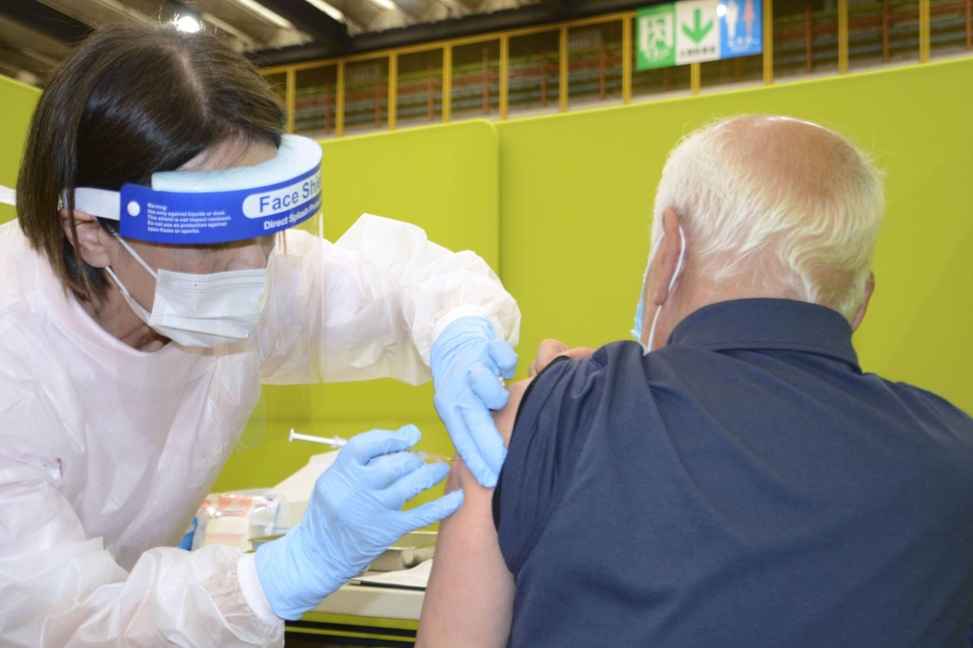 An older resident in the city of Kitakyushu gets a COVID-19 vaccine shot on Monday. | KYODO