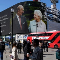 Images of Britain's Queen Elizabeth II and Britain's Prince Philip are displayed on large screens at Piccadilly Circus in central London on Saturday.  | AFP-JIJI