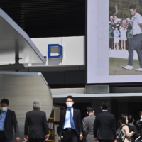 People walk in front of a screen showing the news of Hideki Matsuyama's Masters win on Monday in Tokyo's Akihabara district.  | AFP-JIJI