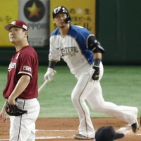 Rakuten pitcher Masahiro Tanaka (left) watches Sho Nakata's first-inning home run for the Fighters on Saturday at Tokyo Dome. | KYODO