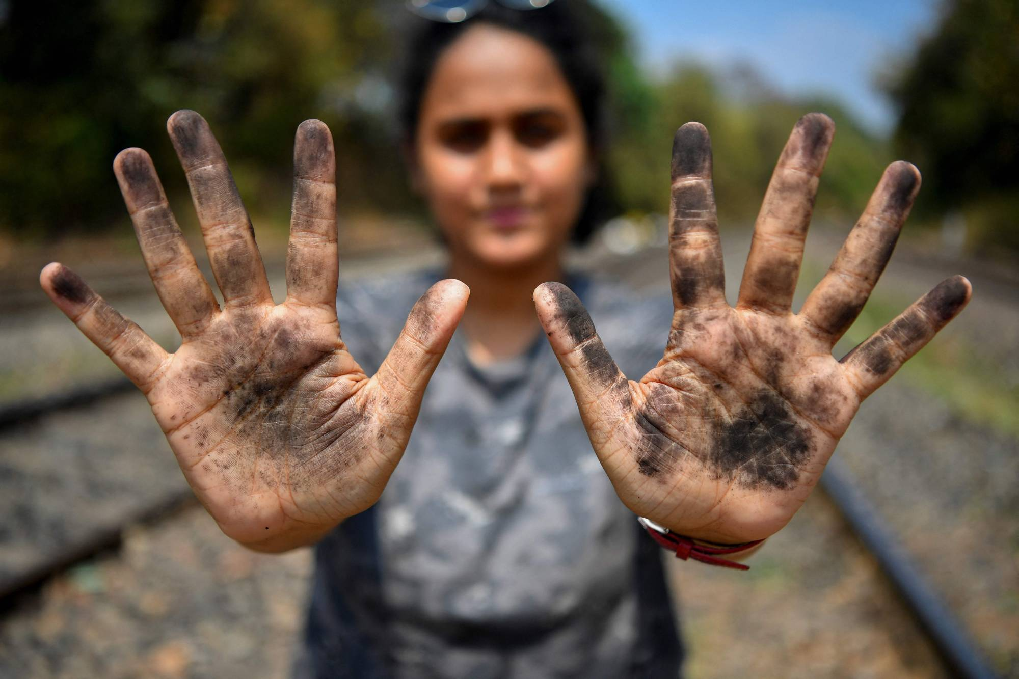 Zoologist Hycintha Aguiar shows her soot-covered hands after handling coal that fell onto railway tracks from a cargo train at the Kulem railway station in Goa state. | AFP-JIJI