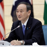 Prime Minister Yoshihide Suga speaks during the virtual Quadrilateral Security Dialogue meeting from his official residence in Tokyo on March 12. | POOL VIA / REUTERS