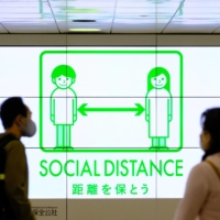 A sign to promote social distancing is placed at a concourse leading to Shinjuku Station in Tokyo. | AFP-JIJI