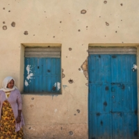 A woman leans on the wall of a damaged house which was shelled as federal-aligned forces entered the city, in Wukro, Ethiopia.  | AFP-JIJI