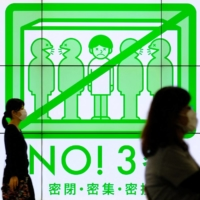 People walk past a public service display promoting social distancing in Tokyo's Shinjuku Ward on Sunday. Fears are growing that COVID-19 variant strains spreading rapidly in the country's west may soon wreak havoc in the Tokyo area as well. | AFP-JIJI