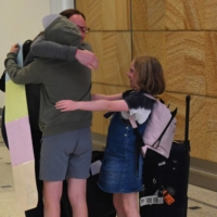Family members from New Zealand reunite at Sydney International Airport on Monday as quarantine-free travel between Australia and New Zealand begins. | AAP / VIA REUTERS