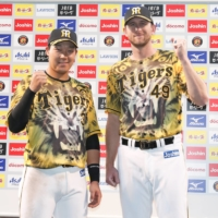 Tigers players Joe Gunkel (right) and Yusuke Oyama pose after their win over the Swallows at Koshien Stadium in Nishinomiya, Hyogo Prefecture, on Sunday. | KYODO