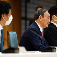 Prime Minister Yoshihide Suga speaks at a government task force meeting with health minister Norihisa Tamura (left) on April 9. | POOL / VIA REUTERS