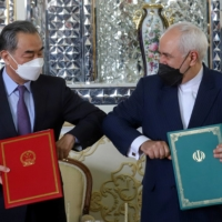 Iranian Foreign Minister Mohammad Javad Zarif and Chinese State Councilor Wang Yi bump elbows during the signing ceremony of a 25-year cooperation agreement, in Tehran on March 27.  | WEST ASIA NEWS AGENCY / VIA REUTERS