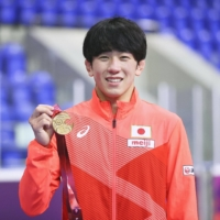 Takuto Otoguro celebrates with his medal after defending his  his men's 65-kg freestyle title at the Asian Wrestling Championships | KYODO