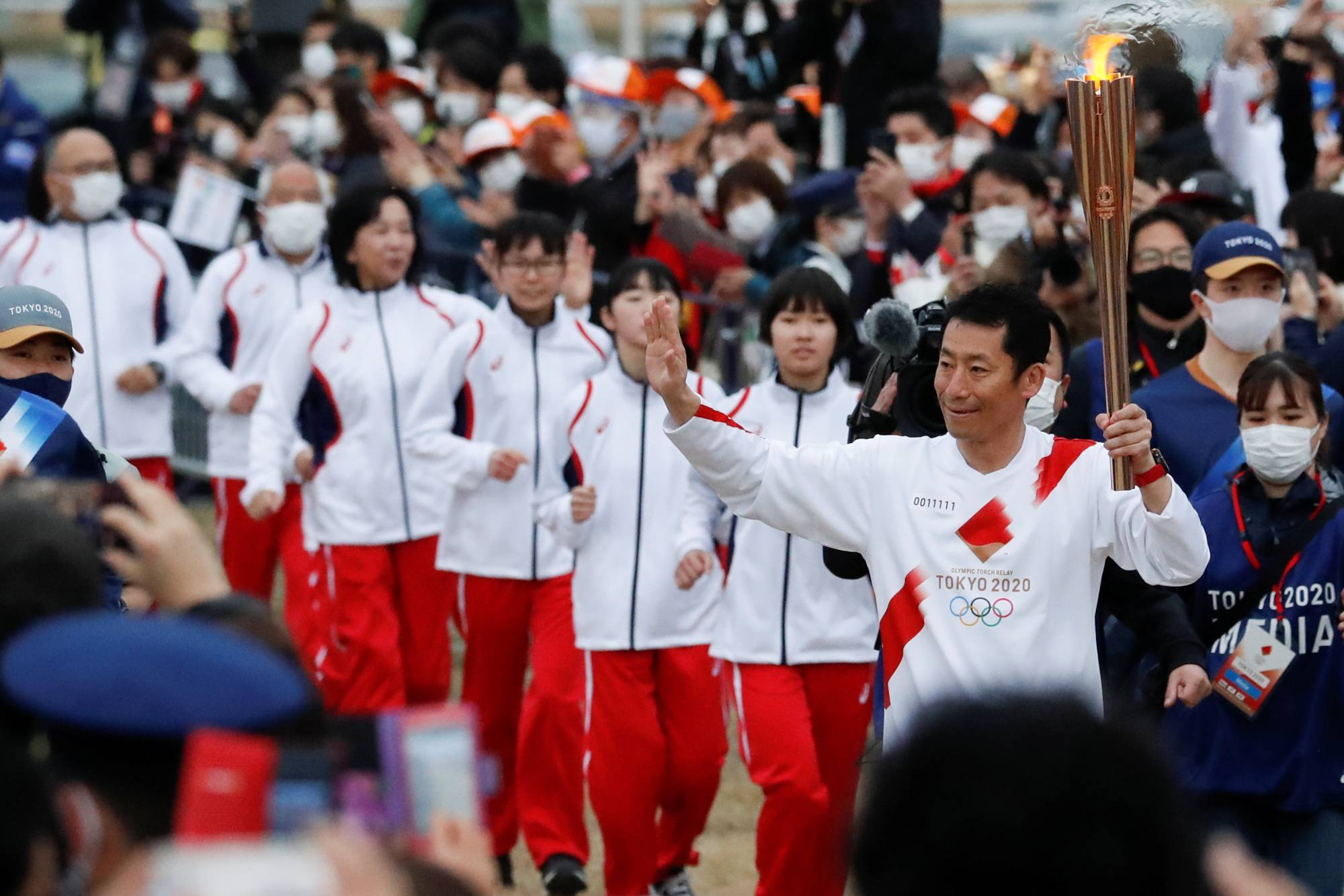 Japanese aerobatics pilot Yoshihide Muroya carries the Olympic torch at Hibarigahara Festival Site in Minamisoma, Fukushima Prefecture, during the last leg of the first day of the Tokyo 2020 Olympic torch relay last month. | REUTERS