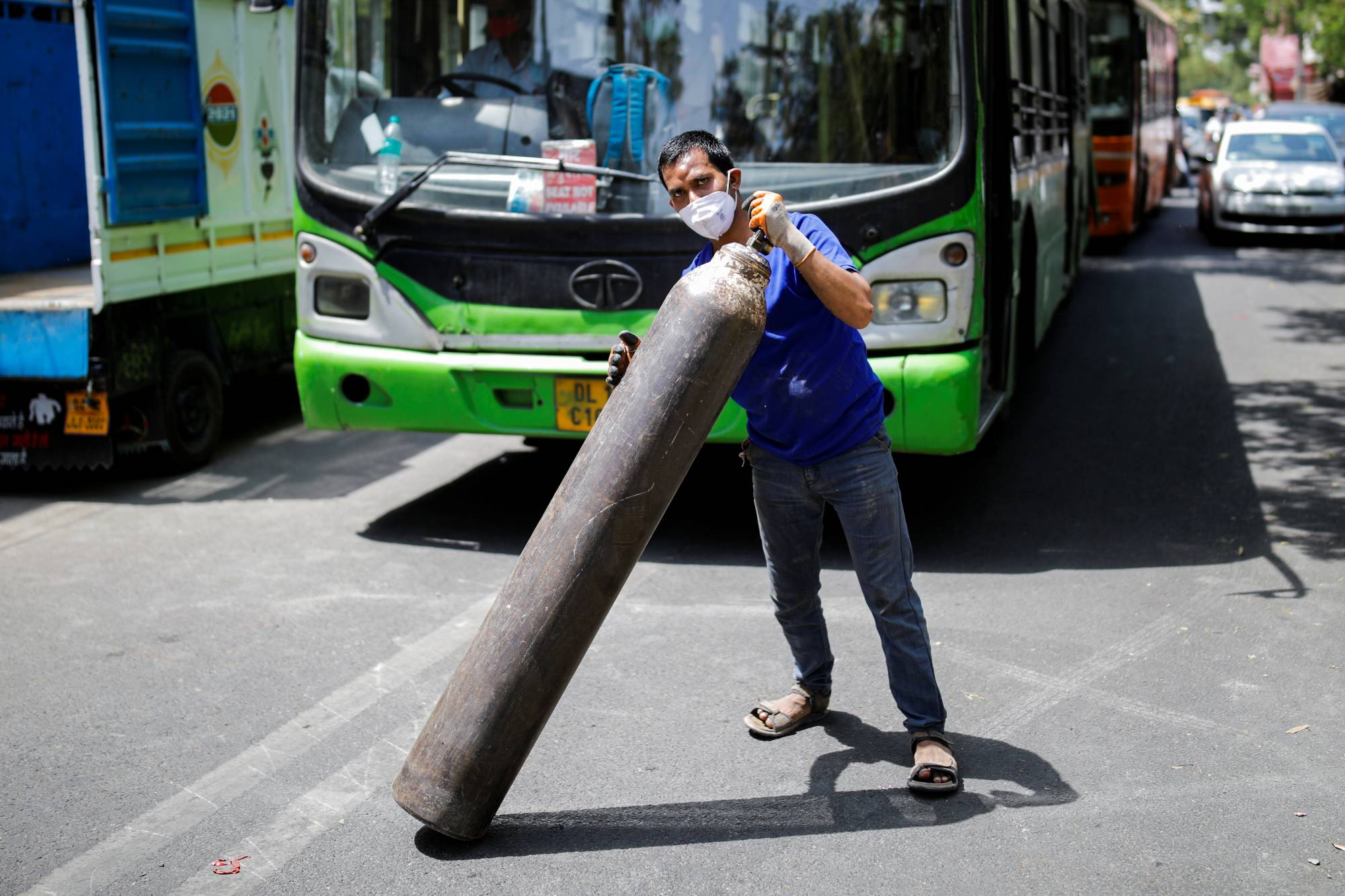 A man carries an oxygen cylinder to load into a truck for a hospital outside a private refilling station in New Delhi on Monday.  | REUTERS